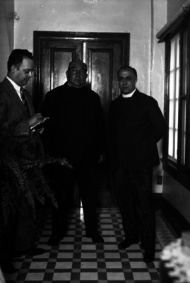Pascual Díaz Barreto con sacerdote y periodista en el pasillo de una iglesia