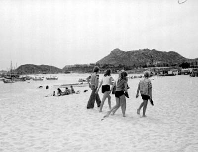 Turistas caminan en la playa