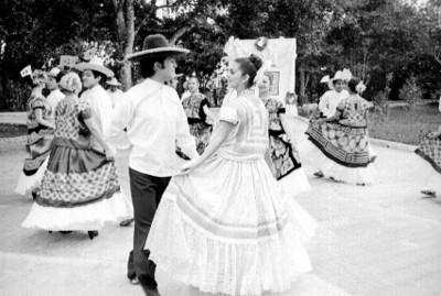 Parejas interpretan baile regional en un parque