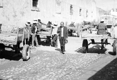 José Chávez Morado Camina Junto a Carretas en una Calle