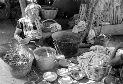 Mujer huave vende vasijas en un tianguis