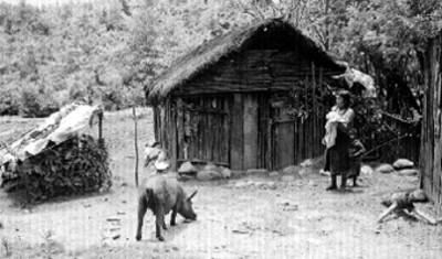 Mujer tzetzal e hijo frente a su vivienda