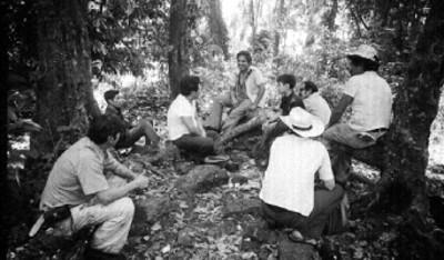 Grupo de hombres sentados bajo unos árboles
