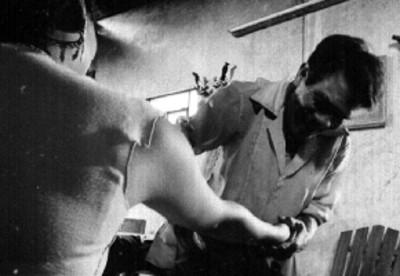 Curandero exáminando el brazo de un paciente