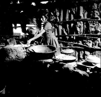 Mujer junto a comal y cazuelas con alimentos