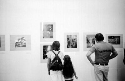 Publico mira exposición fotográfica de Nacho López en el Museo de Arte Moderno