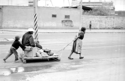 Anciano y niño llevados en un carrito por su familia