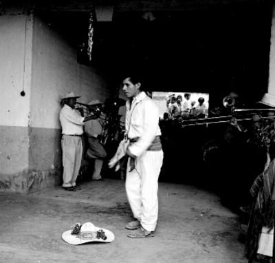 Hombre bailando y a su alrededor músicos tocando