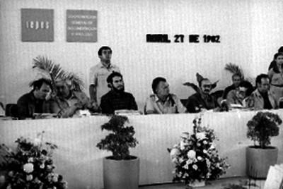 Miguel de la Madrid ante micrófono, durante reunión de consulta popular en un auditorio