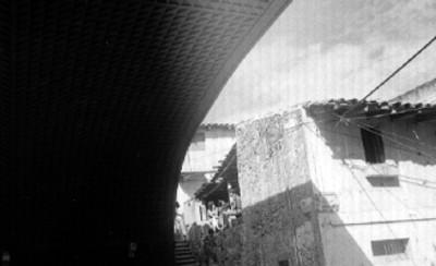 Arco de un puente, al fondo jóvenes en una vivienda de la calle Jesús Diaz