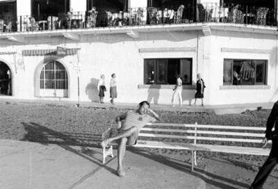 Hombre sentado en una banca del malecón de Puerto Vallarta al fondo un restaurante