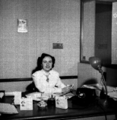 Mujer tras un escritorio en oficina de la Asociación Nacional de la Publicidad, retrato