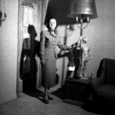 Mujer modela traje junto a una lampara en una sala, retrato
