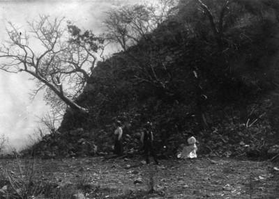 Hombres y mujeres posan bajo montículo en Tepozteco