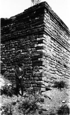 Hombre parado junto a muro prehispánico
