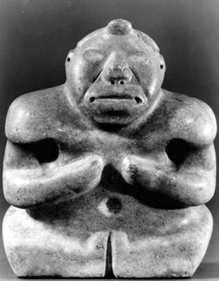 Figura antropomorfa sedente con los brazos en el pecho, vista frontal