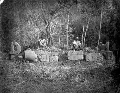 Hombres sentados junto a relieves en el conjunto del cementerio