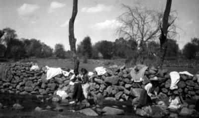 Mujeres indígenas lavan y se bañan en un río