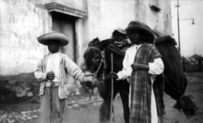 Indígenas nahuas con burro caminan por una calle