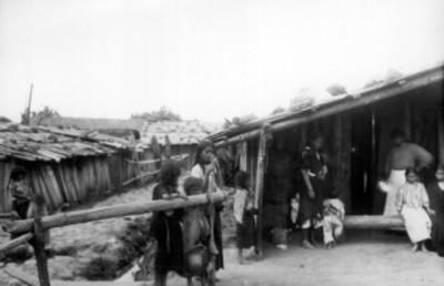 Familia indígena frente a su vivienda, retrato de grupo