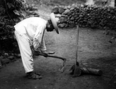 Hombre otomí con herramientas de trabajo en un patio