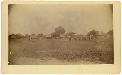 Hombres indígenas montados a caballo en un poblado, retrato de grupo