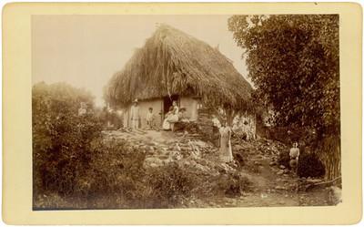Familia indígena afuera de una choza, retrato