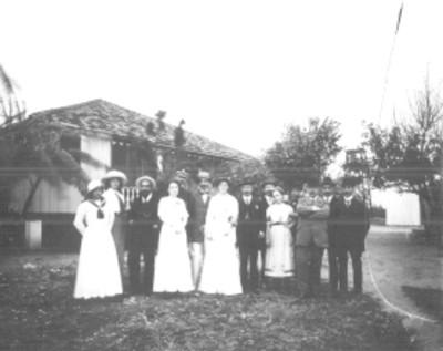 Familia afuera de una casa de campo, retrato de grupo