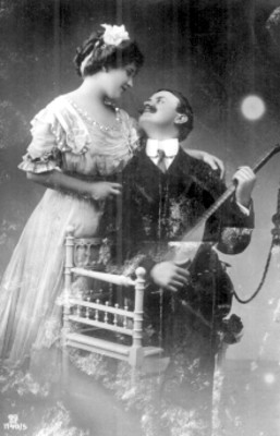 Mujer abraza a hombre que está sentado y sostiene un bandolín
