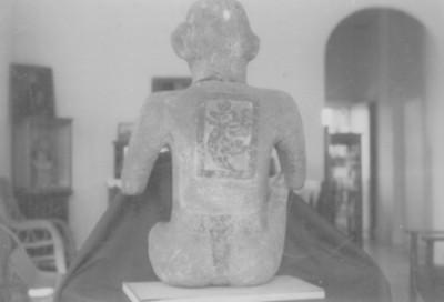 Escultura prehispánica de un personaje sedente con inscripción calendárica en la espalda
