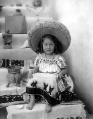 Niña con traje folclórico junto a piezas arqueológicas, retrato