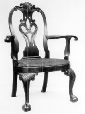 Silla con brazos elaborada en nogal, con asiento tapizado y patas con tallas, expuesta en el Museo Metropolitano de Arte