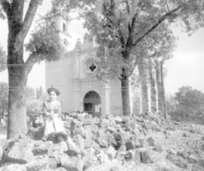 Niño sentado sobre piedras frente a iglesia en San Jerónimo
