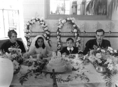 Familia festeja primera comunión de una pareja de niños, retrato
