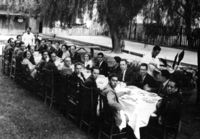 Gente durante banquete en un jardín, retrato de grupo