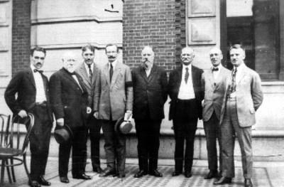 Hombres frente a un edificio, retrato de grupo