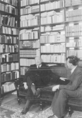 Dos hombres platican en una biblioteca particular