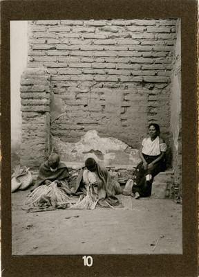 Indígenas tejiendo palma en una casa semi-destruida