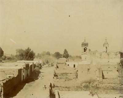 Hombres y mujeres caminan por una calle delimitada por una iglesia y casas de adobe