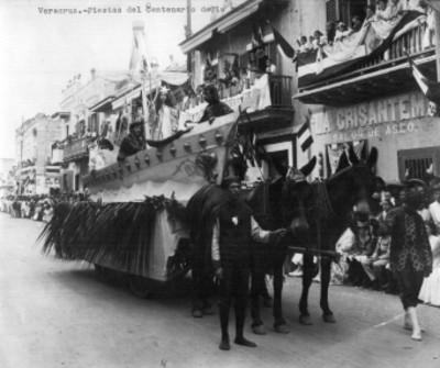 Hombres y mujer con ropajes del siglo XVI desfilan a bordo de un carro jalado por caballos