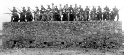 Batallón armado con armas de fuego sobre un muro