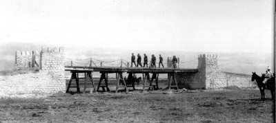 Porfirio Díaz acompañado de autoridades militares caminan por un puente antes de su destrucción