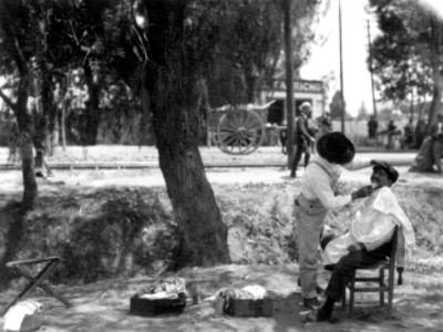 Vista de un peluquero rasura a un hombre en un parque