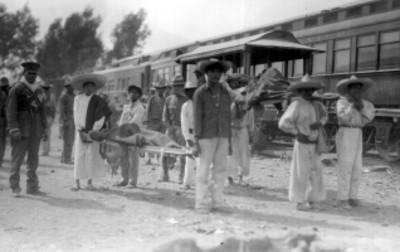 Hombres trasladan en camillas a los soldados heridos