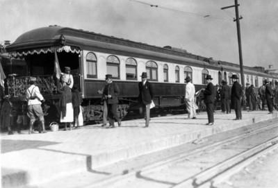 Hombres y mujeres en la estación frente al tren presidencial