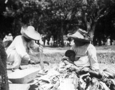 Hombre y mujer artesanos venden artículos de madera en un parque