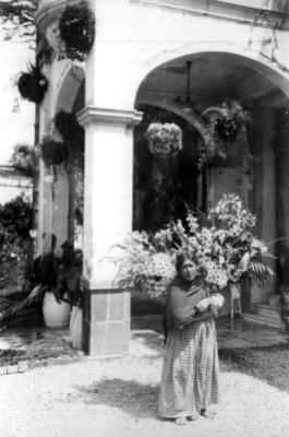 Mujer indígena vendedora de flores, con canasta en el pórtico de una casa