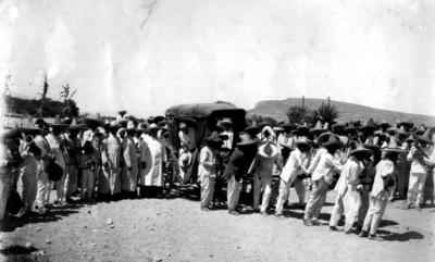 Grupo de feligreses tiran de una carreta con un sacerdote abordo
