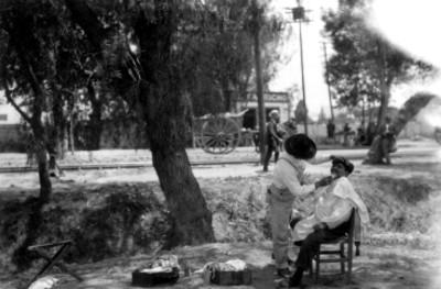 Peluquero y cliente bajo de un árbol