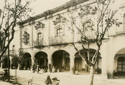 Edificio con balcones y portales frente a una plaza pública